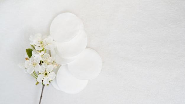Almofadas cosméticas e flor do produto higiênico no fundo branco Foto Premium