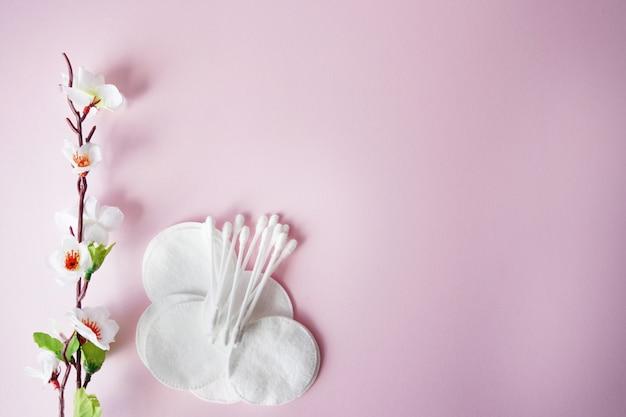 Almofadas de algodão e cotonetes com flores brancas em fundo rosa pastel Foto Premium