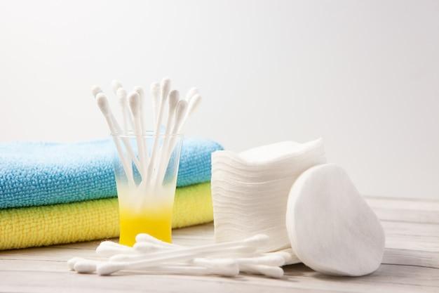 Almofadas de algodão e varas em um copo sobre um fundo claro, ao lado de uma toalha azul e amarela Foto Premium