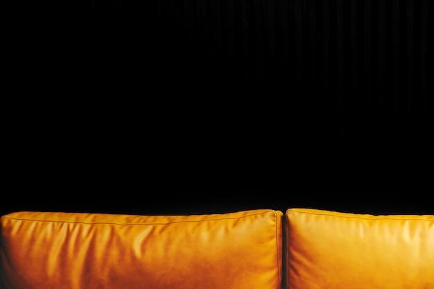 Almofadas de couro de mostarda e fundo preto Foto gratuita