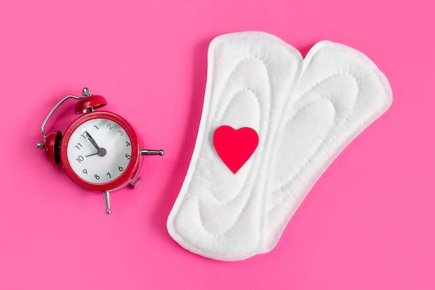 Almofadas menstruais, despertador em um fundo rosa. Foto Premium
