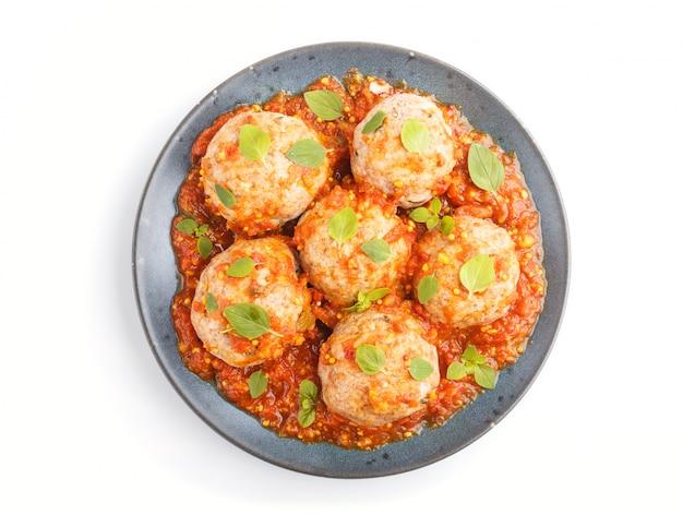 Almôndegas de carne de porco com orégano molho de tomate deixa especiarias e ervas no prato de cerâmico azul, isolado no fundo branco Foto Premium