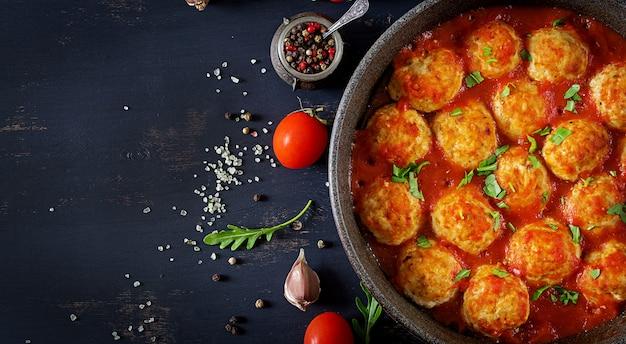 Almôndegas de frango com molho de tomate em uma panela. jantar. vista do topo. fundo escuro. Foto Premium