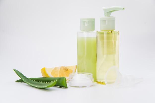 Aloe vera e frasco de spray natural de limão e creme para beleza em fundo branco Foto gratuita