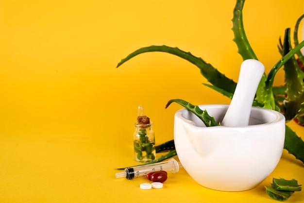 Aloe vera folha, argamassa branca cheia de aloe picado e garrafas de gel de aloe ou infusão. Foto Premium