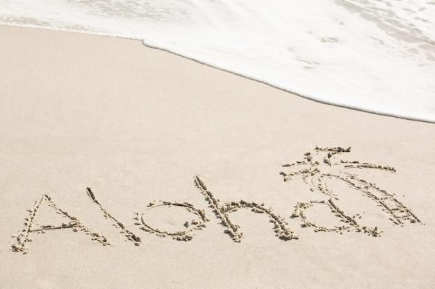 Aloha escrito na areia Foto gratuita