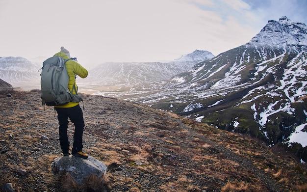 Alpinista com uma mochila tirando fotos das montanhas rochosas cobertas pela neve Foto gratuita