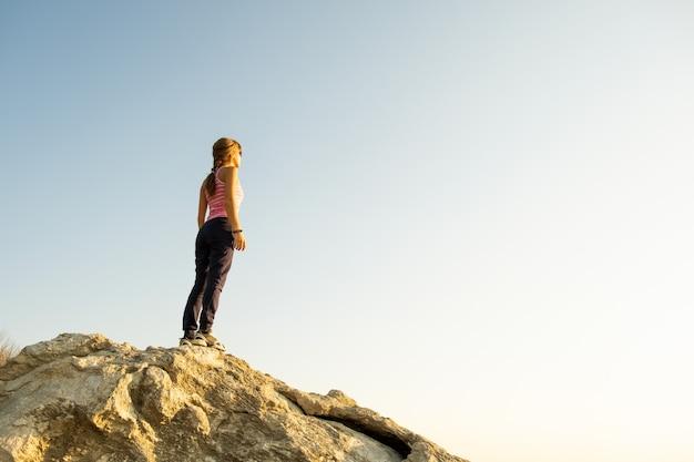 Alpinista de jovem em pé sozinho na pedra grande nas montanhas de manhã Foto Premium