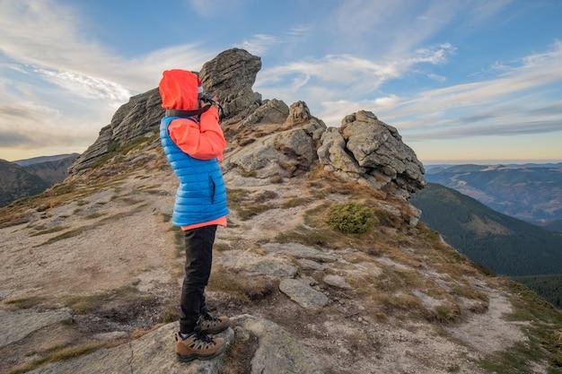 Alpinista de menino criança tirando fotos nas montanhas Foto Premium