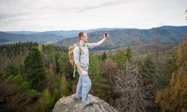 Alpinista de pé no pico de uma pedra e faz selfie no seu telefone Foto Premium