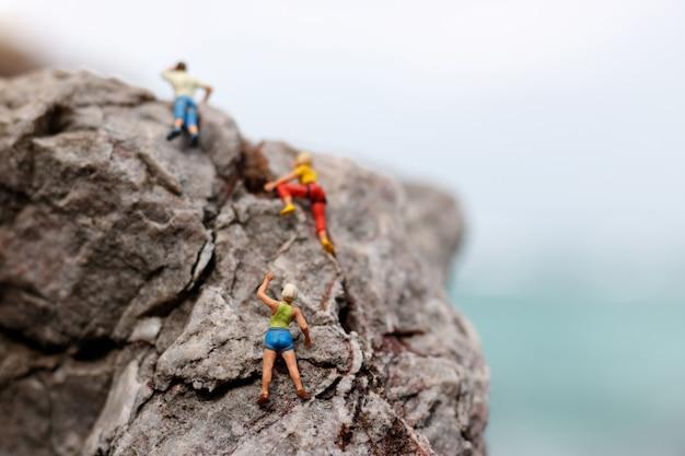Alpinista em miniatura em uma rocha Foto Premium