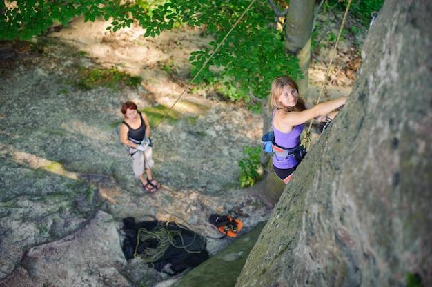 Alpinista feminina escalada com corda em uma parede rochosa Foto Premium