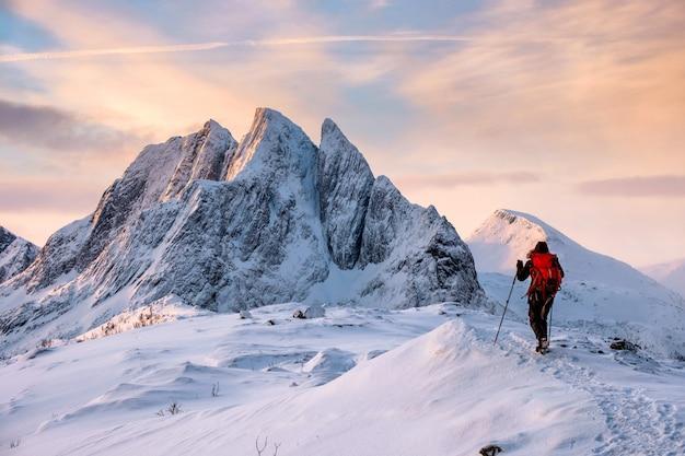 Alpinista homem sobe no topo da montanha de neve Foto Premium