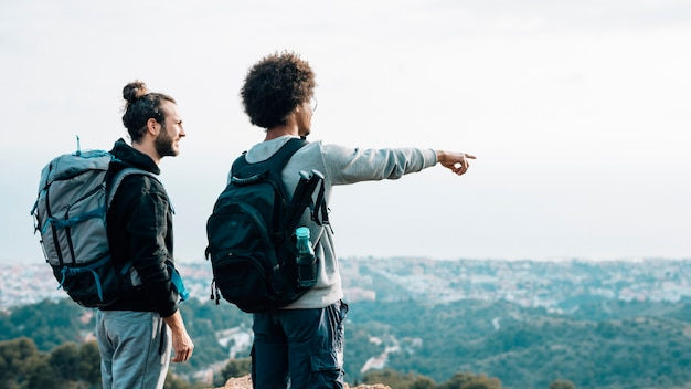 Alpinista masculina, olhando para o dedo apontando jovem africano sobre a paisagem urbana Foto gratuita