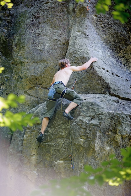 Alpinista muscular sobe na parede do penhasco com corda Foto Premium