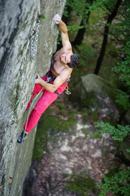 Alpinista muscular sobe no penhasco pendendo no horário de verão Foto Premium
