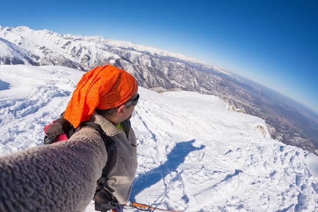 Alpinista tomando selfie na montanha coberta de neve Foto Premium