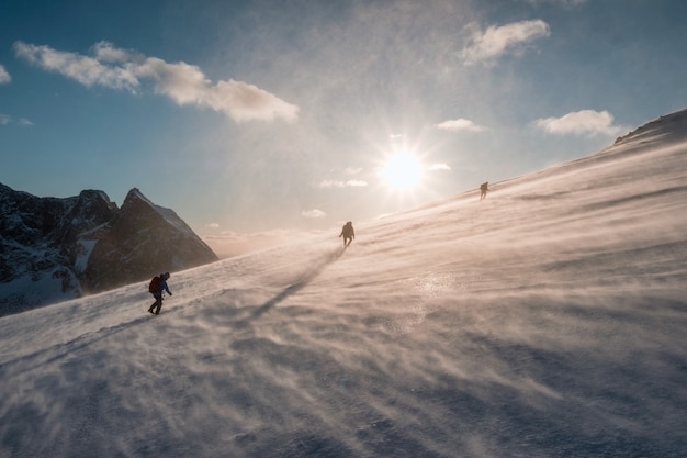 Alpinistas escalando nevasca nevado ao pôr do sol Foto Premium