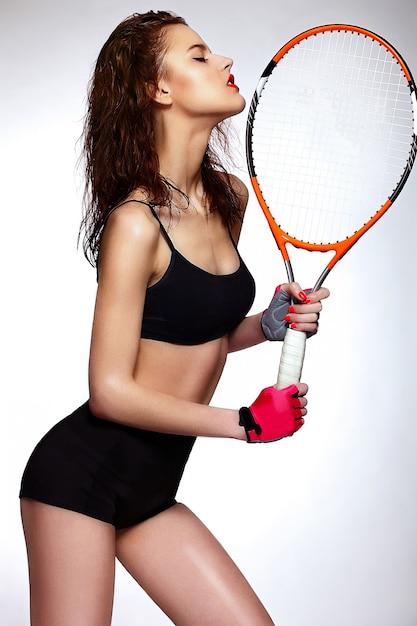 Alta moda look.glamor closeup retrato da bela sexy elegante morena caucasiano jovem profissional tenista modelo de mulher com maquiagem brilhante, com lábios vermelhos com raquete Foto gratuita