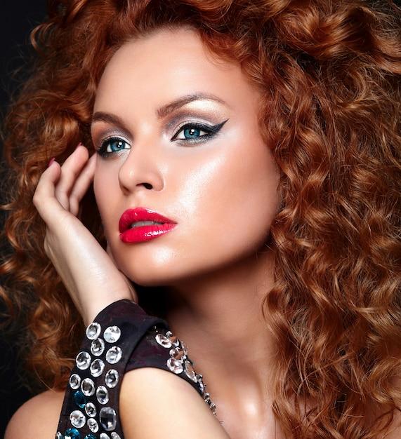 Alta moda look.glamor closeup retrato de modelo ruiva sexy caucasiano mulher jovem e bonita com lábios vermelhos, maquiagem brilhante, com pele limpa perfeita com joias isolada em preto Foto gratuita