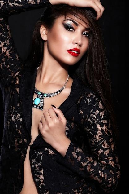 Alta moda look.glamor closeup retrato do modelo sexy caucasiano elegante morena jovem bonita com maquiagem brilhante, com lábios vermelhos, com pele limpa perfeita com jóias em pano preto Foto gratuita