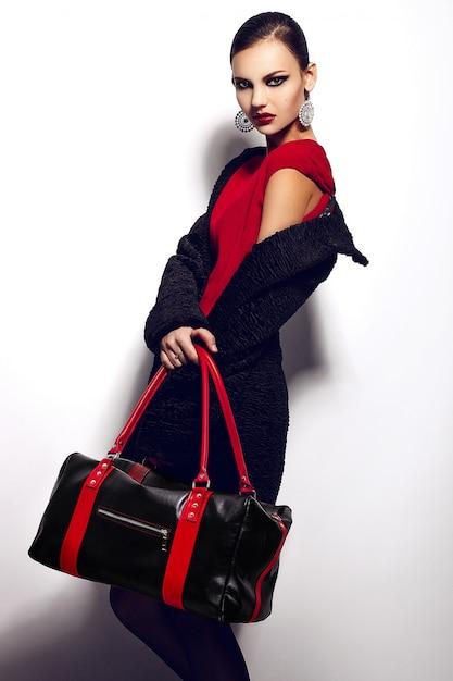 Alta moda look.glamor closeup retrato do modelo sexy caucasiano elegante morena jovem bonita vestido vermelho com maquiagem brilhante bolsa preta, com lábios vermelhos, com pele limpa perfeita em estúdio Foto gratuita