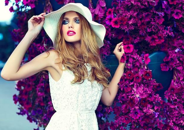 Alta moda look.glamor closeup retrato do modelo sexy elegante loira jovem bonita com maquiagem brilhante e lábios cor de rosa com perfeita pele limpa no chapéu perto de flores do verão Foto gratuita