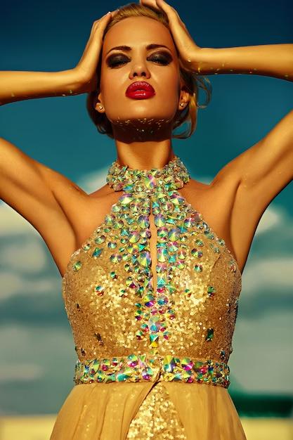 Alta moda look.glamor closeup retrato do modelo sexy elegante loira jovem bonita com maquiagem brilhante e lábios vermelhos com pele limpa banhos de sol perfeita com jóias ao ar livre no estilo da moda Foto gratuita