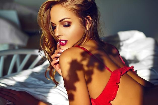 Alta moda look.glamor closeup retrato do modelo sexy elegante mulher jovem e bonita deitado na cama branca com maquiagem brilhante, com lábios vermelhos, com pele limpa perfeita em lingerie vermelha Foto gratuita