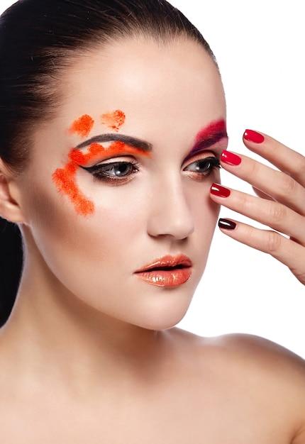 Alta moda look.glamor closeup retrato do modelo sexy morena jovem bonita com lábios laranja e pele limpa perfeita com unhas coloridas Foto gratuita