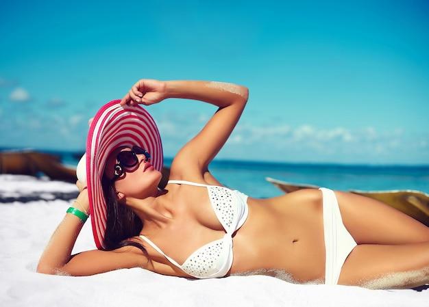 Alta moda look.glamor sexy modelo menina bronzeada em lingerie branca biquíni no chapéu colorido por trás da praia azul água do oceano Foto gratuita