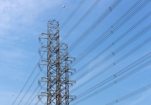 Alta tensão de torres de transmissão de energia no fundo do céu azul Foto Premium