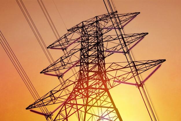 Alta tensão do polo da eletricidade com cabo no céu e na luz solar amarelos conceito da tecnologia. Foto Premium