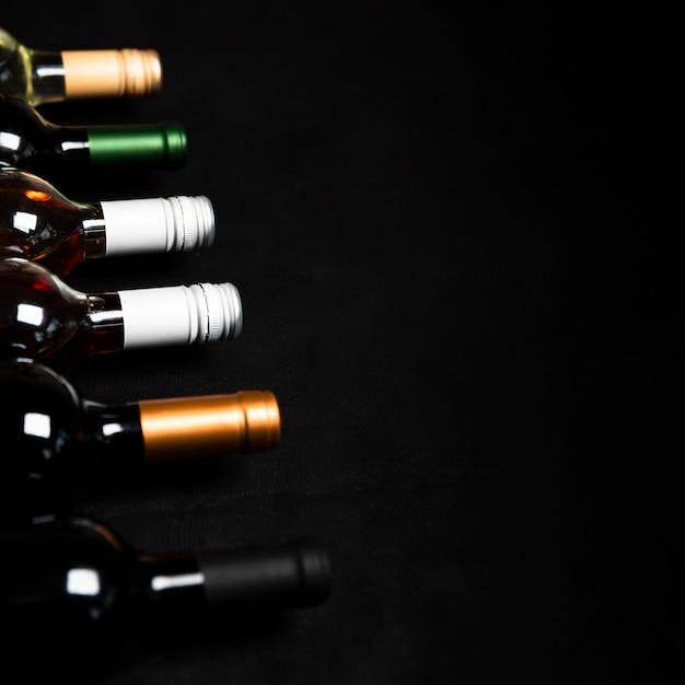 Alta vista garrafas de vinho com fundo preto Foto gratuita