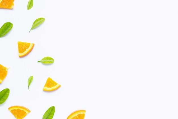 Alta vitamina c, suculenta e doce. fruta alaranjada fresca com as folhas verdes no branco. Foto Premium