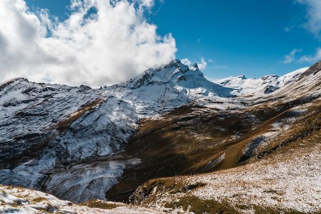 Altas montanhas rochosas cobertas de neve sob um céu azul claro na suíça Foto gratuita