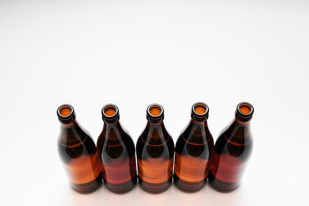 Alto ângulo alinhado garrafas de cerveja no fundo branco, com espaço de cópia Foto gratuita