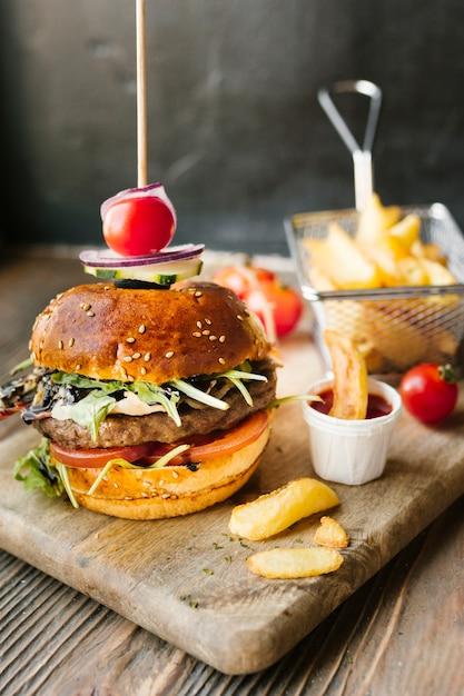 Alto, ângulo, close-up, de, hambúrguer, e, frita, ligado, tábua madeira Foto gratuita
