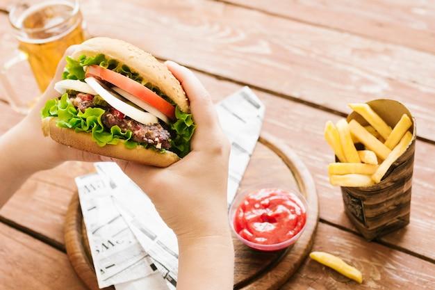 Alto ângulo, close-up, mãos, segurando, hambúrguer, com, hambúrguer, com, frita Foto gratuita