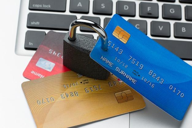 Alto ângulo de bloqueio com cartões de crédito em cima do laptop Foto gratuita