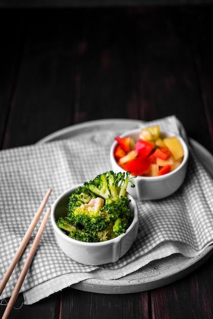 Alto ângulo de brócolis e pimentão em copos no prato Foto gratuita
