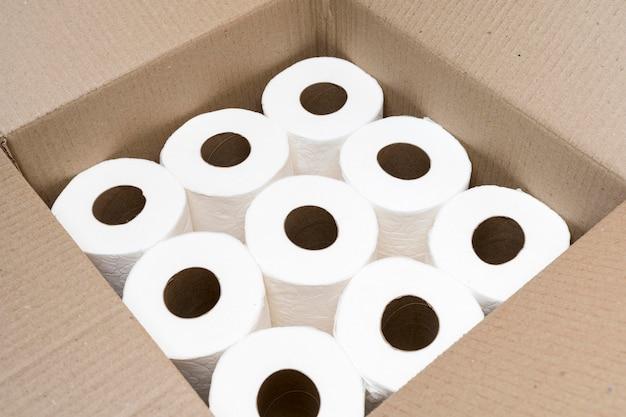 Alto ângulo de caixa de papelão com rolos de papel higiênico Foto gratuita