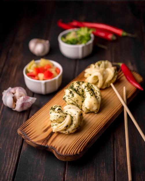 Alto ângulo de comida asiática na placa de madeira com alho Foto gratuita