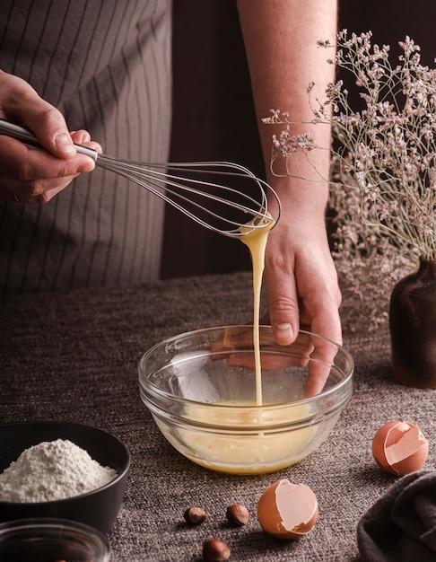 Alto ângulo de cozinheiro mexendo ovos na tigela Foto gratuita