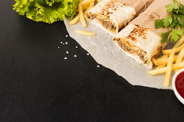 Alto ângulo de delicioso kebab com batatas fritas e espaço de cópia Foto gratuita