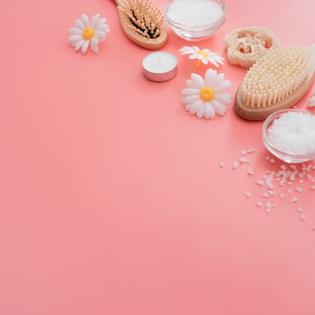 Alto ângulo de escovas de spa e flores de camomila Foto gratuita