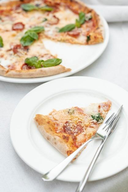 Alto ângulo de fatia de pizza em um prato fundo liso Foto gratuita
