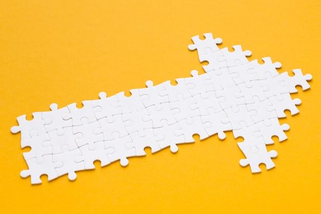 Alto ângulo de flecha feita de peças de quebra-cabeça Foto Premium