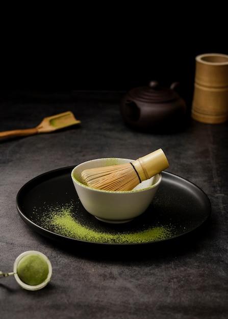 Alto ângulo de matcha chá em pó em uma tigela com peneira e placa Foto gratuita