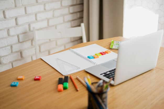 Alto ângulo de mesa com laptop pronto para aulas on-line Foto gratuita